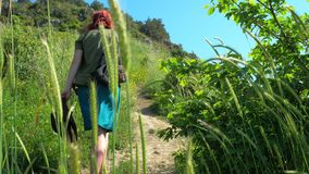 Red-haired girl in a cowboy hat and a backpack walks on a mountain path. A young red-haired traveler girl in a cowboy hat walks along a mountain path overgrown stock video