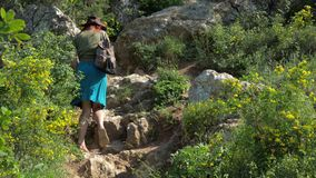 Red-haired girl in a cowboy hat with a backpack walks on a mountain trail. stock footage