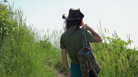 Red-haired girl in a cowboy hat with a backpack walks on a mountain trail. A young red-haired traveler girl in a cowboy hat with a backpack walks along a stock footage