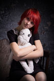 Red-haired girl and doll on a chair royalty free stock photo