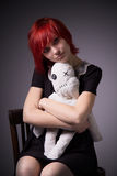 Red-haired girl and doll on a chair royalty free stock image