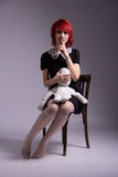 Red-haired girl and doll on a chair stock image