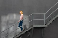 Red-haired girl down the stairs. Red-haired girl in blue jeans and pink down the metal stairs on the gray background gray wall. Redhead Daylight Girl Fashion Stock Photos