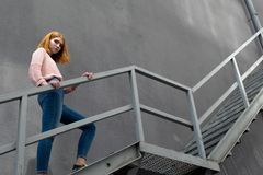Red-haired girl down the stairs Royalty Free Stock Images