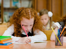 Red-haired girl drawing in copybook in classroom Stock Image