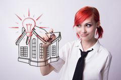 Red-haired girl draws a house drawing royalty free stock images