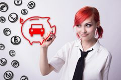 Red-haired girl draws a token cars and piggy bank Royalty Free Stock Photography