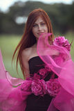 Red-haired girl in the dress of flowers. Red-haired girl in a flowing gown of flowers stock photos