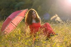 Red- haired girl in a red dress. And with red umbrella in nature Stock Image