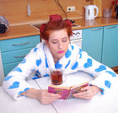 The red-haired girl in a dressing gown in kitchen wound hair curlers, guided black to tea and sat down to read the novel Stock Image