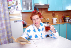 The red-haired girl in a dressing gown in kitchen wound hair curlers, guided black to tea and sat down to read the novel Stock Photography