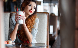 The red-haired girl drinking coffee in cafe royalty free stock images