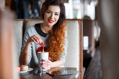 The red-haired girl drinking coffee in cafe stock image