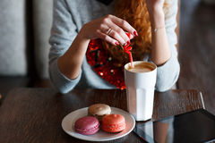 The red-haired girl drinking coffee in cafe. A bright ,beautiful woman with curly red hair,red lipstick,beautiful makeup,red nail Polish,sitting alone at a table stock photography