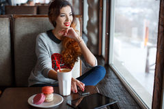 The red-haired girl drinking coffee in cafe. A bright ,beautiful woman with curly red hair,red lipstick,beautiful makeup,red nail Polish,sitting alone at a table royalty free stock photos