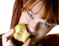 Red haired girl eating  appl closeup. Red haired girl eating green apple and looking ahead closeup Stock Photos