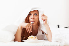 Red-haired girl eating biscuit in  bed Stock Photos