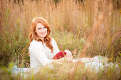 Red haired girl in a field smiling Stock Photos