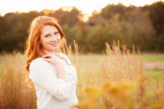 Red haired girl in a field smiling Royalty Free Stock Photography