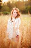 Red haired girl in a field smiling Royalty Free Stock Images