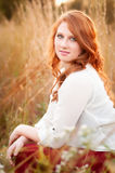 Red haired girl in a field smiling Royalty Free Stock Image