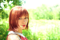 Red-haired girl with a flower in his mouth Stock Images