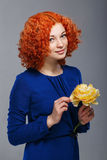 Red-haired girl and flowers Royalty Free Stock Image