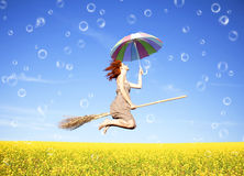 Red-haired girl fly with umbrella. Over field and bubbles around Royalty Free Stock Images