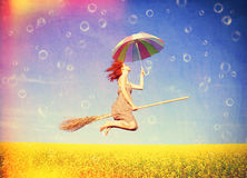 Red-haired girl flying with umbrella. Over field and bubbles around Stock Images