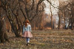 Red-haired girl with freckles in a park. Spring or Autumn. Happy carefree childhood stock images