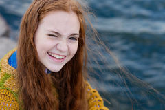Red-haired girl with freckles sitting on the seashore royalty free stock images