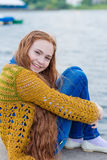 Red-haired girl with freckles sitting on the seashore stock photo