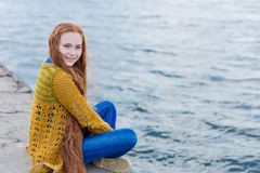 Red-haired girl with freckles sitting on the seashore stock photos