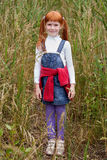 red-haired girl with freckles standing in tall grass Stock Image