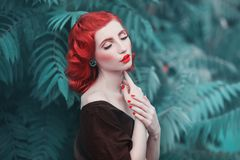 Red-haired girl in a free flying dress and retro hairstyle against a summer background. stock photography