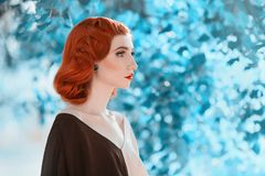 Beautiful red-haired retro girl with clean healthy skin and blue eyes. Fashion vintage model Stock Image