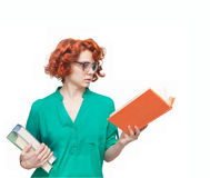 Red-haired girl in glasses with books Stock Images