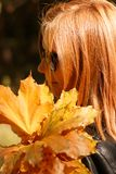Red-haired girl in glasses holds yellow leaves royalty free stock image