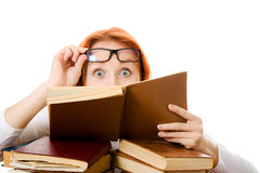 Red-haired girl in glasses reads book. Stock Photography