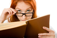 Red-haired girl in glasses reads book. Royalty Free Stock Photos