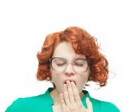 Red-haired girl in glasses yawning Royalty Free Stock Image