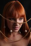 The red-haired girl and gold jewelry Royalty Free Stock Images