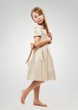 Red-haired girl in a golden dress Stock Photos