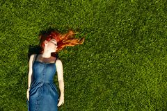 Red haired girl on the grass Royalty Free Stock Photography