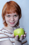 Red haired girl with green apple Stock Images