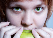 Red haired girl with green apple royalty free stock images