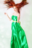 Red-haired girl in a green dress with flowing hair Royalty Free Stock Photography