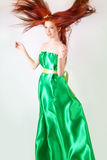 Red-haired girl in a green dress with flowing hair Royalty Free Stock Photo