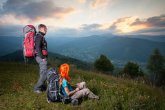 Red-haired girl and guy with backpacks at sunset Stock Photos