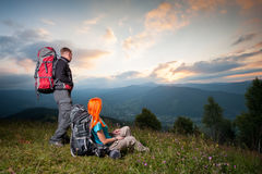 Red-haired girl and guy with backpacks at sunset Stock Photography